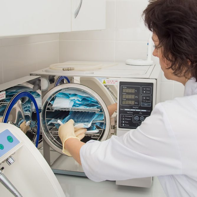 Instrument sterilization in dentistry, nurse loading instrumenst in sterilizer